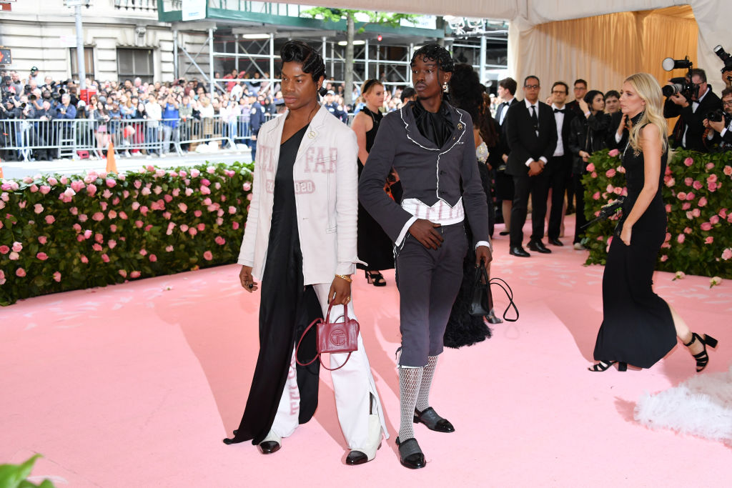 Telfar Clemens in white jacket and Ashton Sanders in gray and black suit