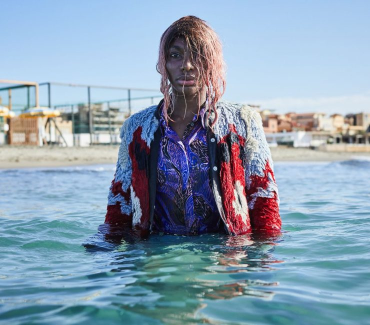 Michaela Coel in water with colorful jacket.